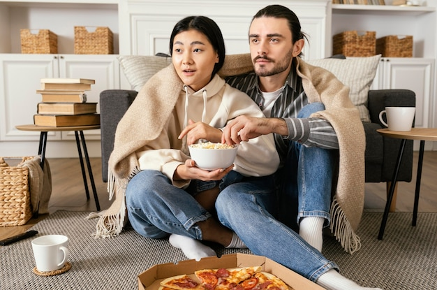 Casal em cobertor assistindo a um filme e comendo