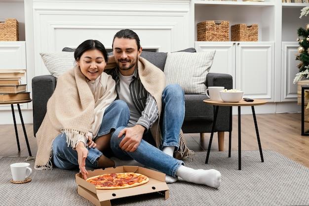 Casal em cobertor assistindo tv e comendo pizza
