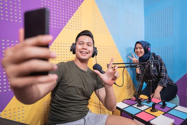 Casal em estúdio de podcast tirando uma selfie com o telefone