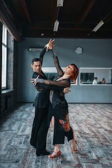 Casal em fantasias no treinamento de dança ballrom em sala de aula. parceiros masculinos e femininos em pares profissionais dançando no estúdio