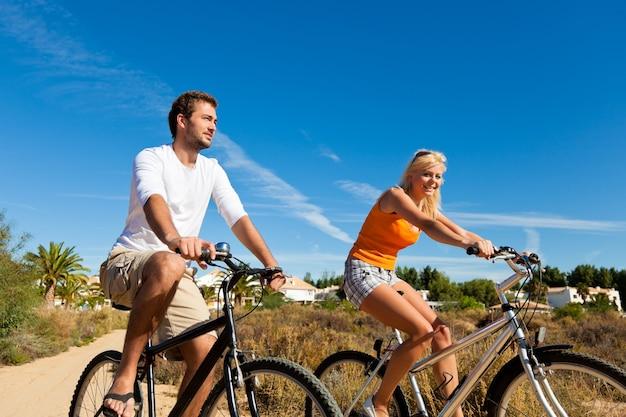 Casal em férias, andar de bicicleta na praia