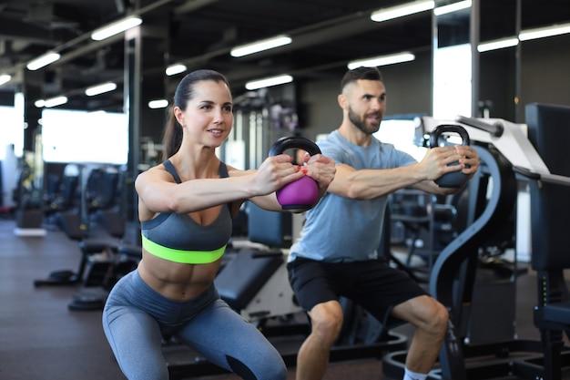 Casal em forma e musculoso focado em levantar um halter durante uma aula de exercícios em uma academia.