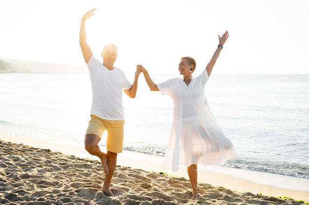 Casal em foto completa de mãos dadas na praia