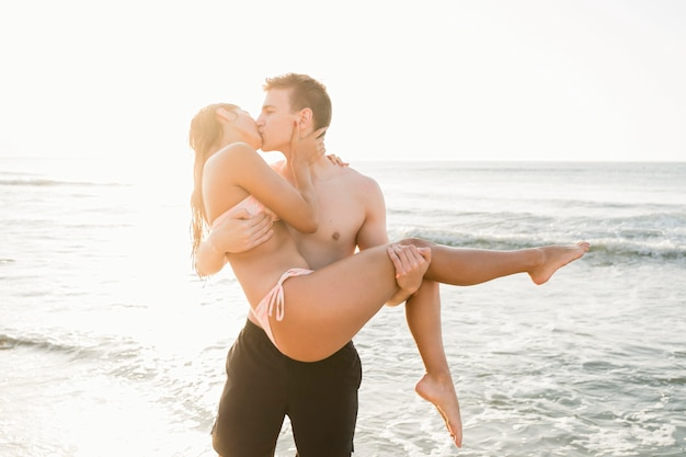 Casal em foto média se beijando na praia
