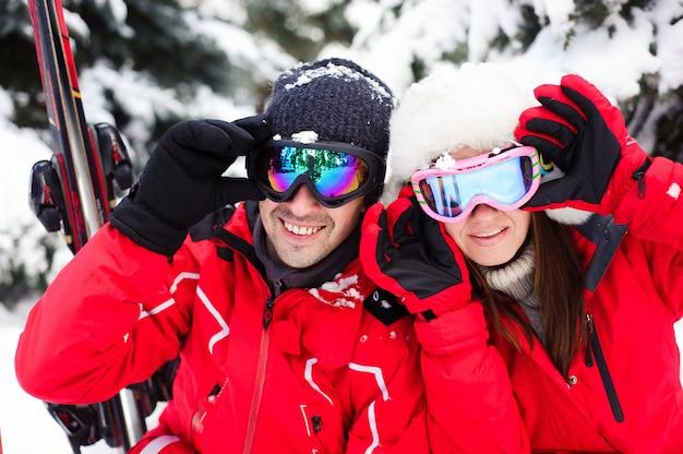 Casal em jaquetas brilhantes, preparando-se para esquiar juntos na floresta de inverno.