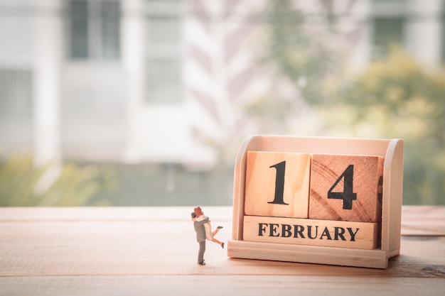 Casal em miniatura com calendário de madeira. 14 de fevereiro. dia dos namorados.