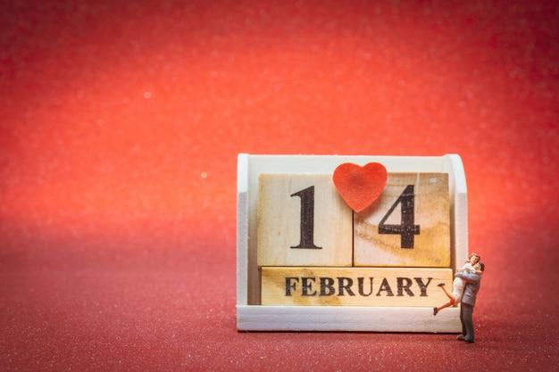 Casal em miniatura com calendário de madeira