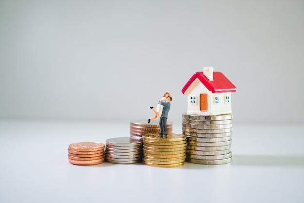 Casal em miniatura e casa na pilha de moedas