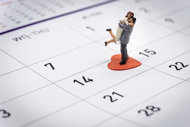 Casal em miniatura em pé no calendário