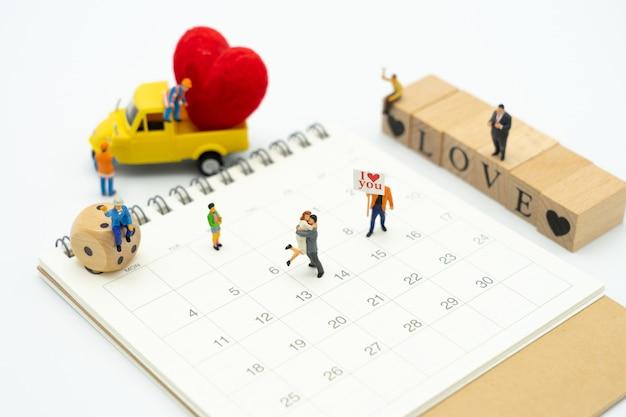 Casal em miniatura pessoas em pé com coração vermelho é a promessa de amor.
