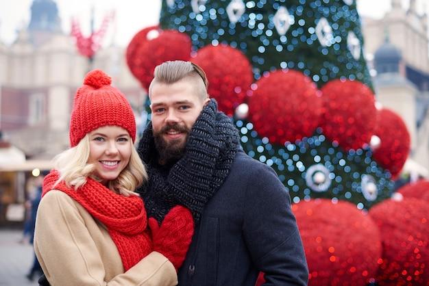 Casal em pé ao lado da árvore de natal