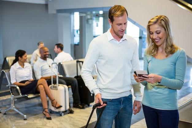 Casal em pé com bagagem segurando smartphone e cartão de embarque