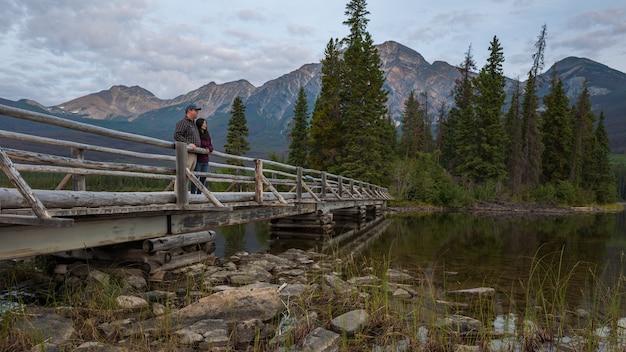 Casal em pé em uma ponte romanticamente olhando para uma bela paisagem