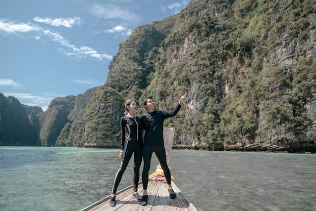 Casal em pé na frente de um barco longtail fazendo um passeio, mar no mar de andaman da lagoa de pileh, ilhas phi phi, tailândia.