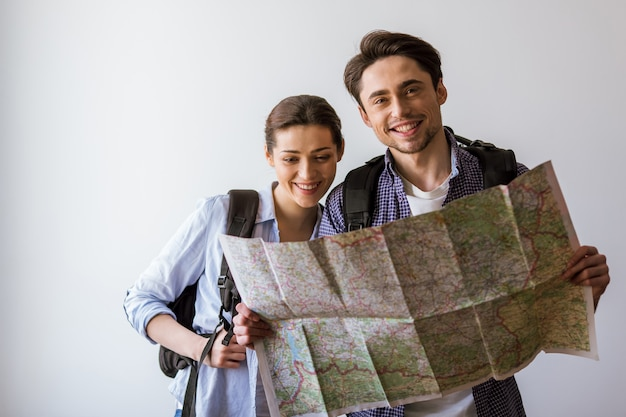 Casal em roupas casuais e com mochilas segurando um mapa.