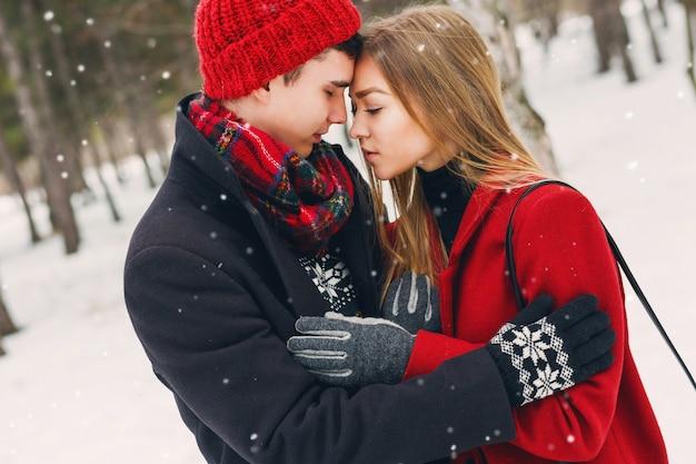 Casal em roupas de inverno, abraçando em um dia nevado