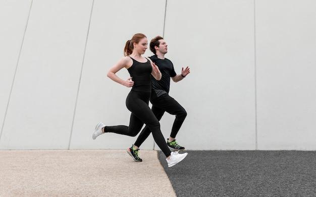 Casal em roupas esportivas fazendo exercícios ao ar livre