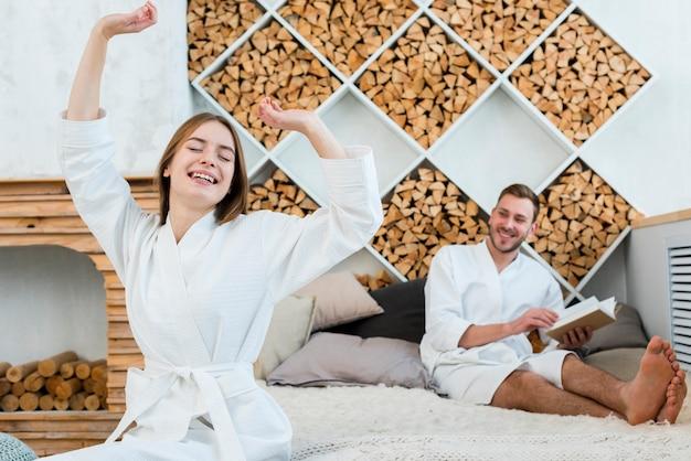 Casal em roupões de banho acordando na cama