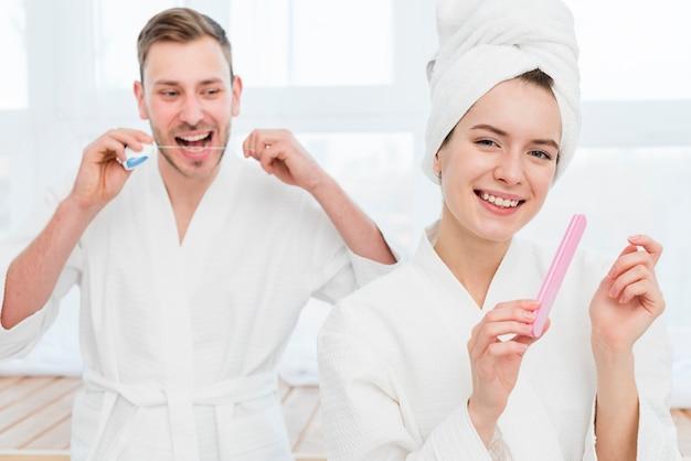 Casal em roupões de banho usando fio dental e lixa de unha
