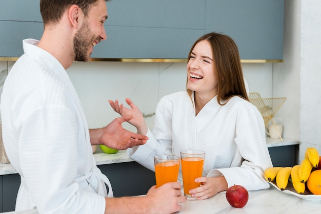 Casal em roupões, desfrutando de suco na cozinha