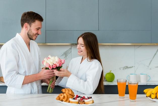 Casal em roupões sorrindo e segurando o buquê de tulipas