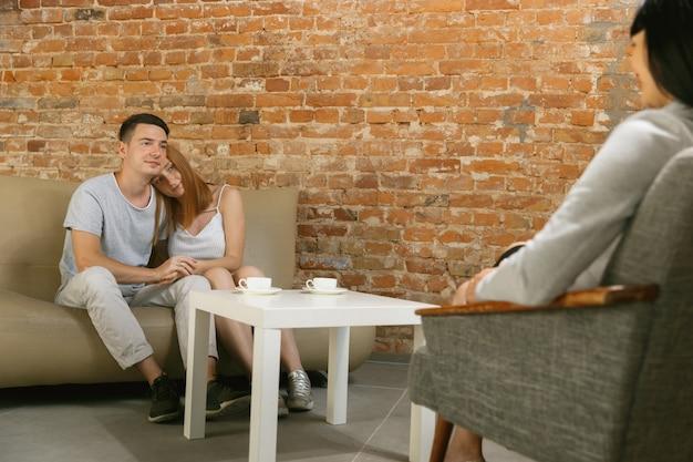 Casal em terapia ou aconselhamento matrimonial. psicólogo, conselheiro, terapeuta ou consultor de relacionamento dando conselhos. homem e mulher sentados em uma sessão de psicoterapia. família, conceito de saúde mental.