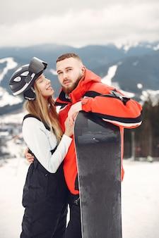 Casal em ternos de snowboard. desportistas em uma montanha com uma prancha de snowboard nas mãos no horizonte. conceito em esportes