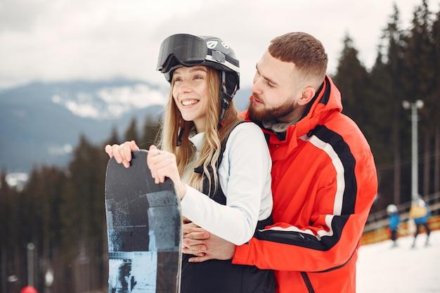Casal em ternos de snowboard. esportistas em uma montanha com uma prancha de snowboard nas mãos no horizonte. conceito em esportes