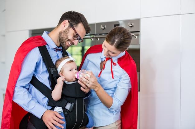 Casal em traje de super-heróis, alimentar o leite para a filha