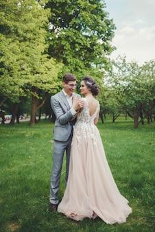 Casal em trajes de casamento com o pano de fundo do parque