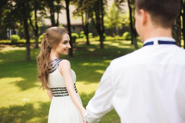 Casal em trajes de casamento está nas mãos contra o pano de fundo do campo ao pôr do sol, a noiva e o noivo