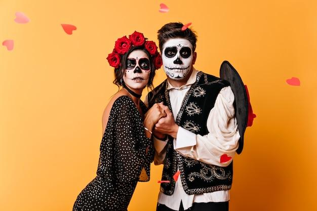 Casal em trajes de halloween, de mãos dadas na parede laranja.
