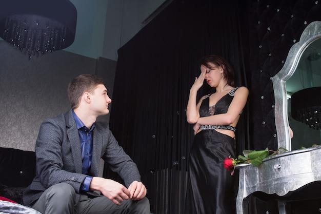 Casal em trajes formais discutindo com uma mulher segurando a cabeça nas mãos