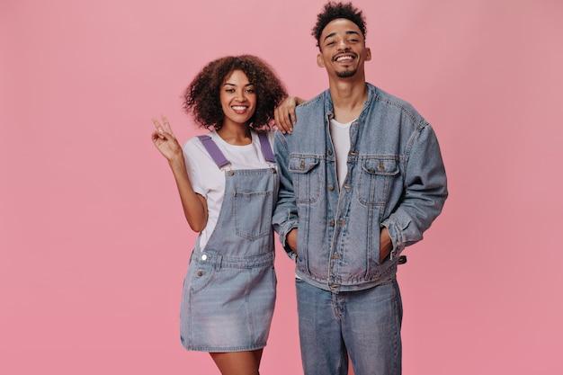 Casal em trajes jeans posando na parede rosa