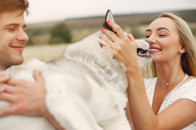 Casal em um campo de outono brincando com um cachorro