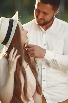 Casal em um campo. morena em uma camiseta branca. pares sentados na grama.