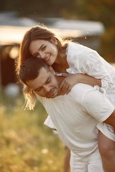 Casal em um campo. mulher de vestido branco. fundo do sol.
