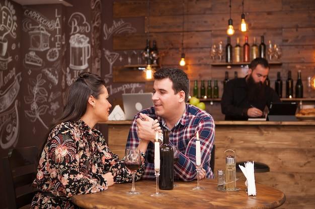 Casal em um encontro sentado em um pub hipster bebendo vinho tinto. comemoração.