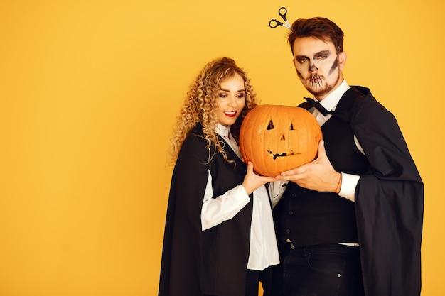 Casal em um fundo amarelo. mulher vestindo fantasia preta. senhora com maquiagem de halloween.