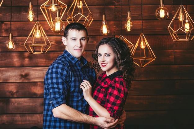 Casal em um interior moderno e festivo com luzes brilhantes