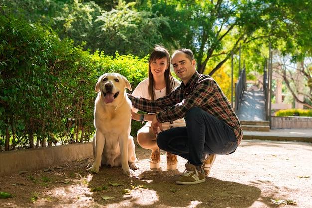 Casal em um parque, eles estão com um cachorro labrador