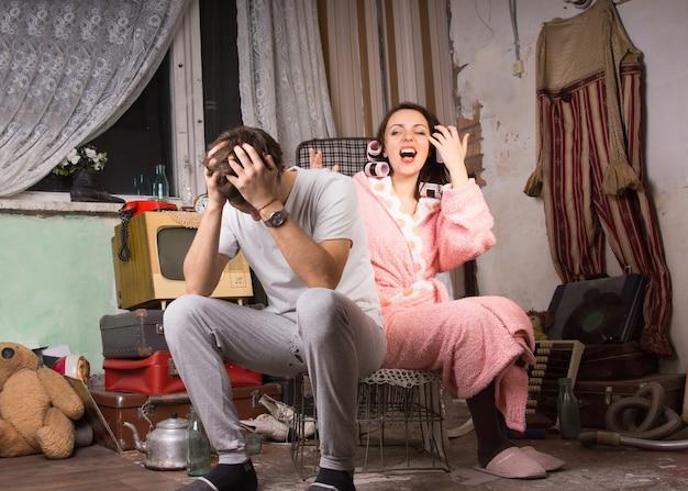 Casal em um quarto miserável discutindo enquanto estão sentados em uma caixa de arame com o homem segurando a cabeça dele nas mãos e a esposa em roupão expressando sua raiva