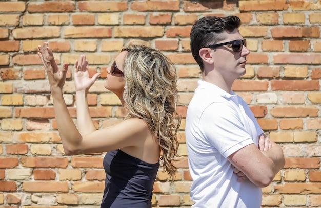 Casal em uma briga e a garota levantando as mãos