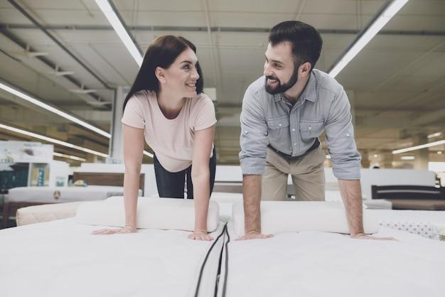 Casal em uma grande loja inspeciona o colchão antes de comprar.