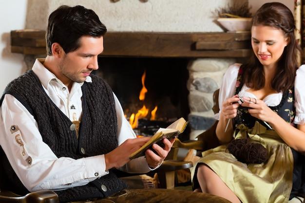 Casal em uma tradicional cabana na montanha com lareira, tricotando e lendo a bíblia