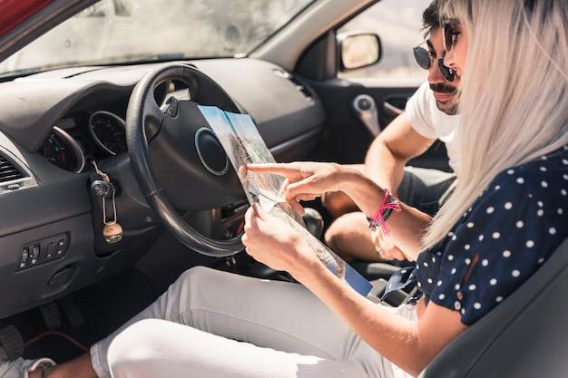 Casal em viagem de férias sentado dentro do carro olhando mapa