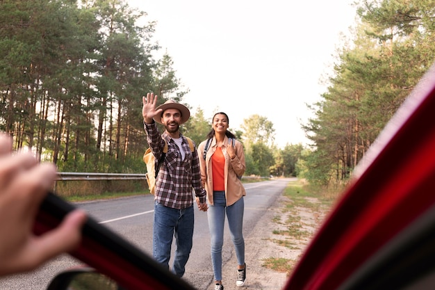 Casal em visão frontal procurando carro durante a viagem