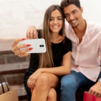Casal embaçado tomando selfies no shopping