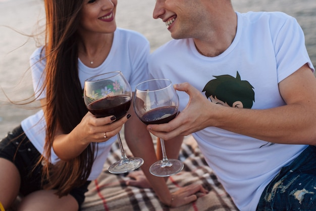 Casal emocional bebe vinho de copos altos na natureza.