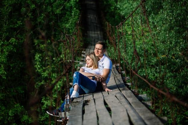 Casal emocional feliz abraçando na história de bridge.love de madeira. um homem e uma mulher apaixonada, caminhando ao ar livre no verão. feliz sorrindo sonhando casal juntos ao ar livre. atividade data romântica. momento romântico